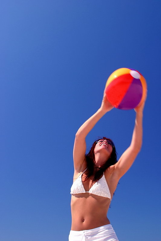Woman catching beach ball with blue sky behind