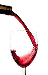 Red Wine Pouring into Glass on White